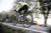 Low angle view of cyclist riding mountain bike with speed effect — 图库照片