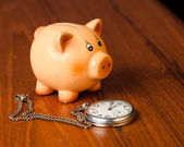 Piggy bank and pocket watch — Stock Photo