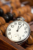 Pocket watch next to abacus — Stock Photo