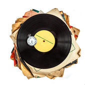 Stack of old scratched dusty vinyl records and pocket watch — Stock Photo