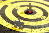 Jigsaw Puzzle Piece on Old Yellow Target — Stock Photo