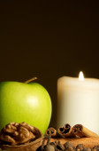 Green apple, cinnamon, walnut and a candle — Stock Photo