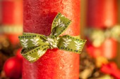 Red candle with green ribbon — Stock Photo