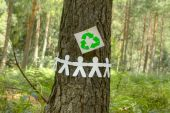 Recycle sign with paper men on a tree — Stock Photo