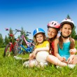 Three little girls sitting on meadow — Stock Photo #52641501