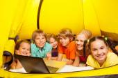 Six kids lay in yellow tent — Foto Stock