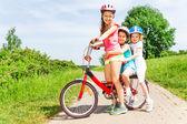 Tres chicas sentadas en bicicleta — Foto de Stock