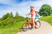 Two little girls sit on bicycle — Stock Photo