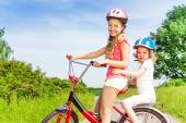Two little girls sitting on bicycle — Stock Photo