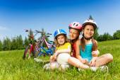 Three little girls sitting on meadow — Stock Photo