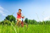 Teenage girl with bicycle on meadow — Stock Photo