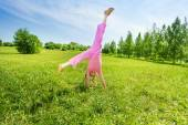 Active girl making flip on grass — Stock Photo
