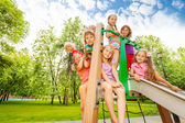 Happy kids on playground chute — Stock Photo