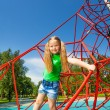 Cute girl balancing on red rope — Stock Photo #52709427