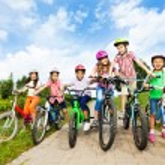 Happy kids in colorful bike helmets — Stock Photo #52715503