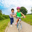 Boy helps girl to ride bike — Stock Photo #52715527