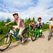 Постер, плакат: Kids in helmets riding bikes