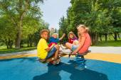Children sitting on playground carousel — Stock Photo