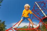 Actieve jongen staat op rode koord — Stockfoto