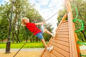 Boy climbs on wooden construction — Stock Photo