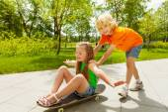 Rapaz empurra menina skate — Foto Stock