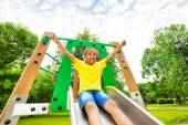 Boy with hands up on children chute — Stock Photo