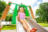 Funny girl on playground chute — Stock Photo