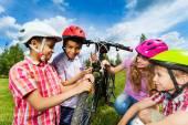 Smiling kids repair bike together — Stock Photo