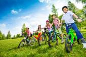 Row of children holding bikes — Stock Photo