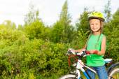 Cheerful girl in helmet holds bike — Stock Photo