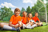 Children sit together with football — Stock Photo