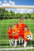 Different height kids stand with football — Stock Photo