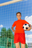 Boy with ball stands near woodwork — Stock Photo