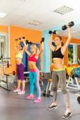 Three girls exercising with dumbbells  — Stock Photo