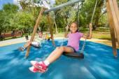 Kids swinging on playground — Stock Photo