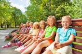 Group of kids sitting on bench — Stock Photo
