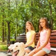 Two happy girls sitting on bench — Stock Photo #52852705