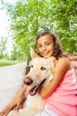 Beautiful teenage girl hugs dog — Stock Photo