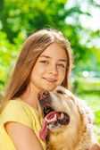 Happy teenage girl hugging dog — Stock Photo