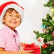 Boy in Santa hat with presents — Stock Photo #60426095