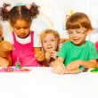 Boys and girls play with plasticine — Stock Photo #60426303