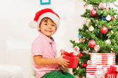 Boy in Santa hat with presents — Stock Photo