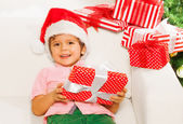 Boy in Santa hat with presents — Stok fotoğraf