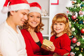 Family sitting near Christmas tree — Stock Photo