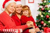 Mother and grandmother give present to girl — Stock Photo