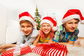 Kids in Santa hats lying on floor — Stock Photo