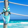 Stripped bikini hanging on ropes of pier — Stock Photo #60706827