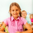 Girl sitting at desk in classroom — Stock Photo #60709557