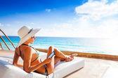 Woman reading e-book near pool — Stock Photo