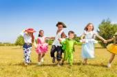 Happy kids running wearing costumes — Stock Photo